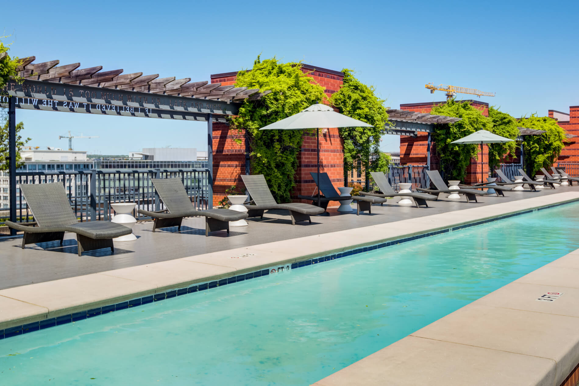 Pool with row of chaise lounge chairs and side tables