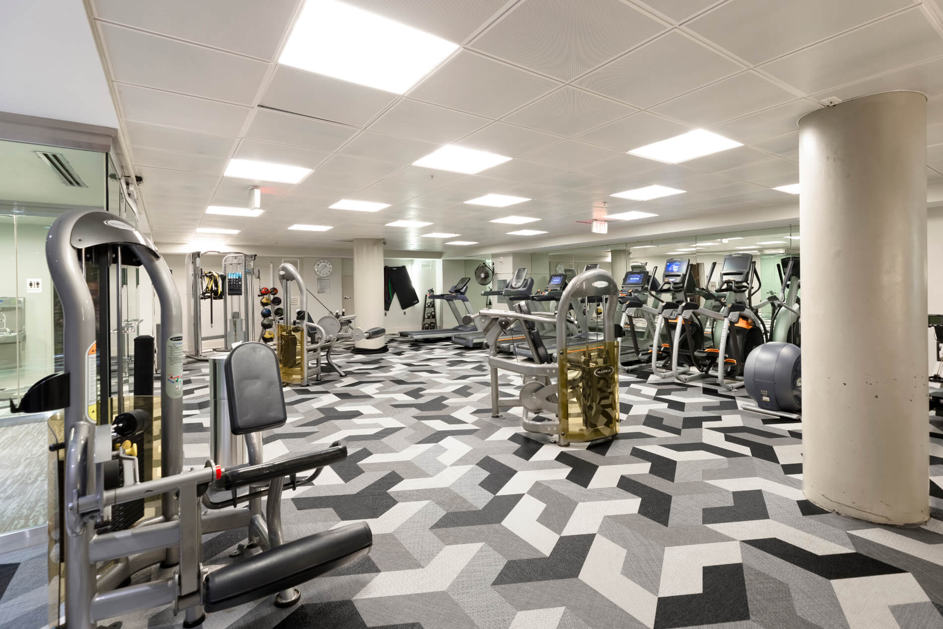 Gym with workout equipment, ceiling lights and patterned flooring