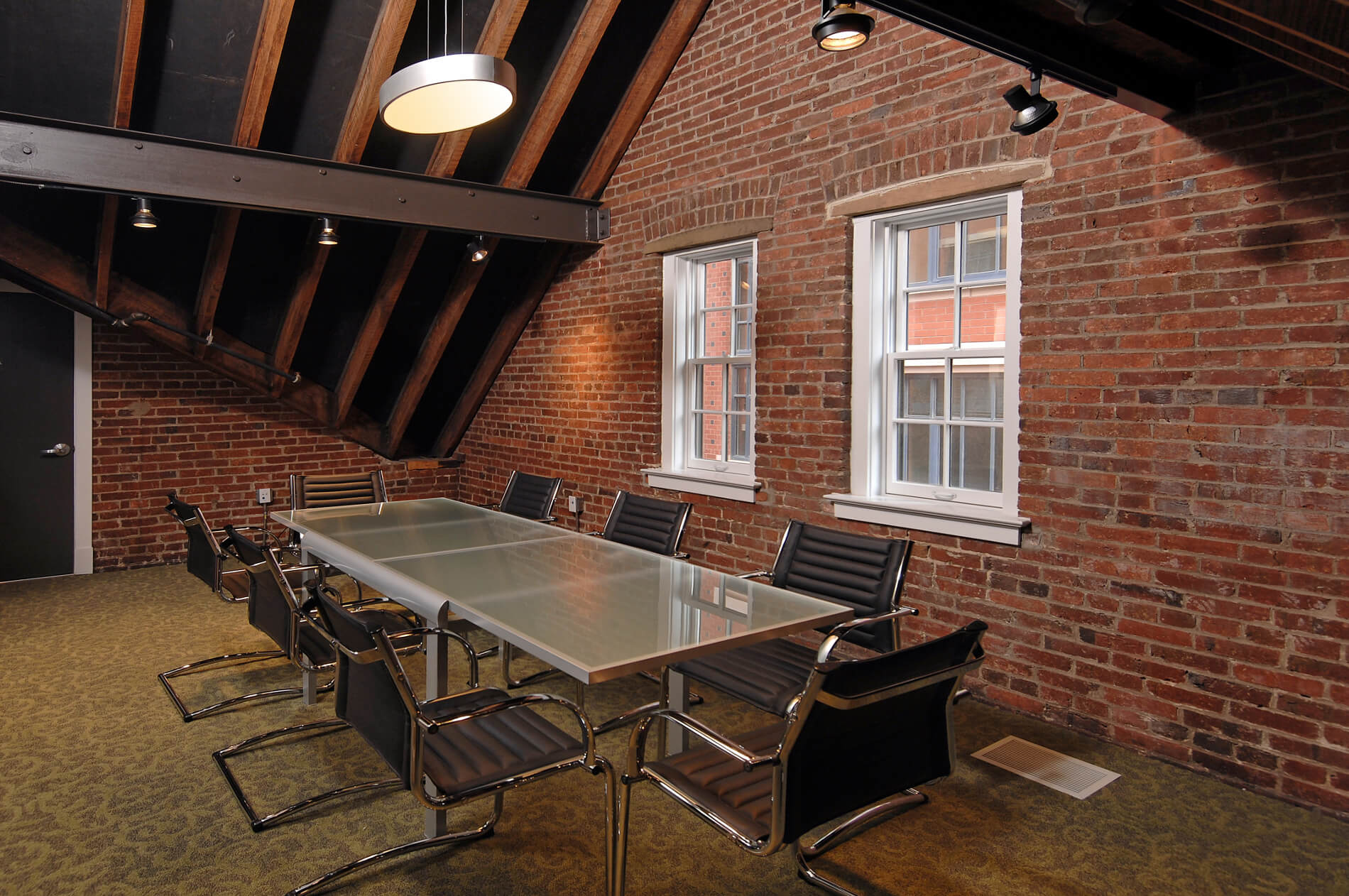 Table with eight chairs in brick room with exposed wooden rafters