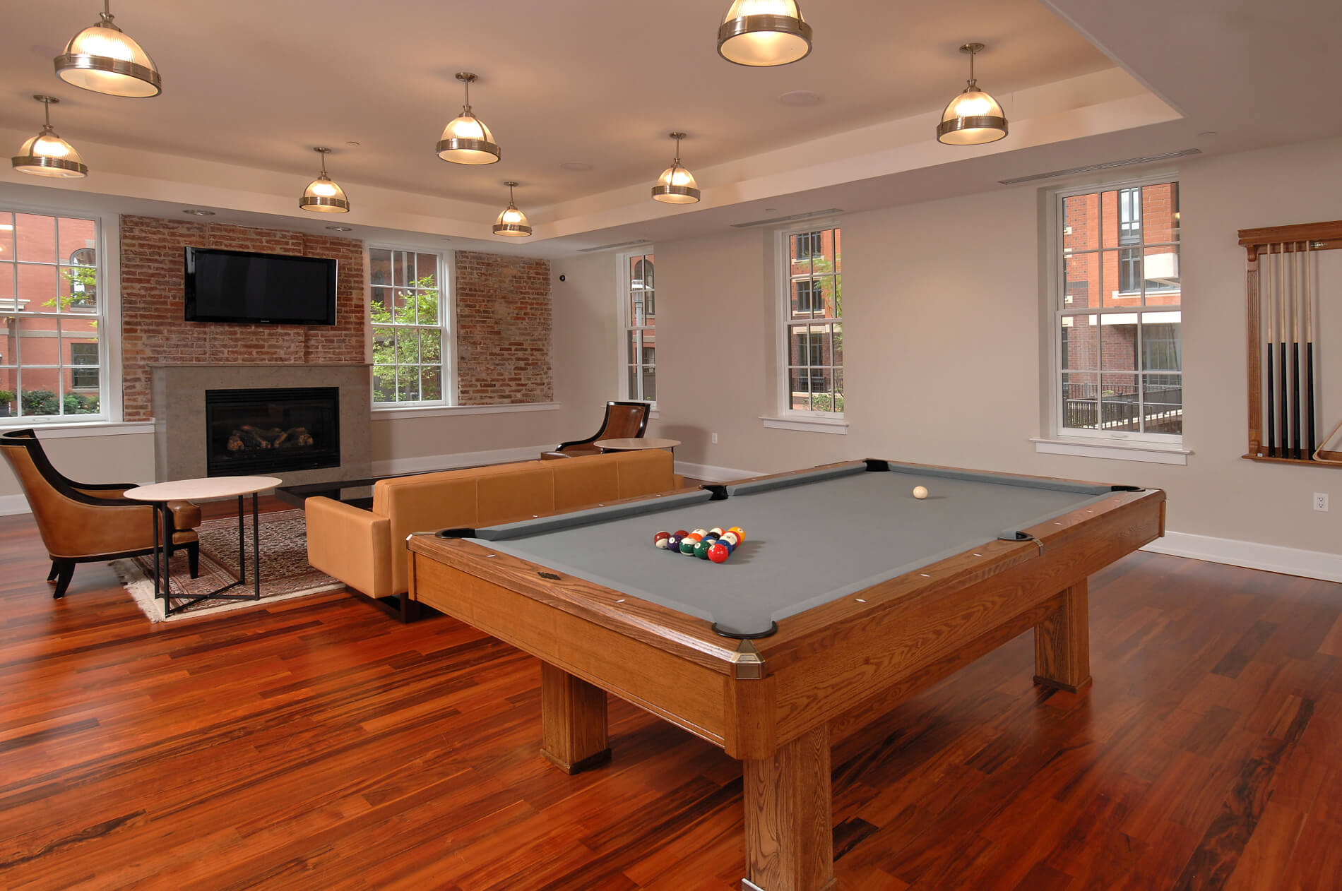 Pool table with seating, pendant lighting, fireplace and views of the outdoors