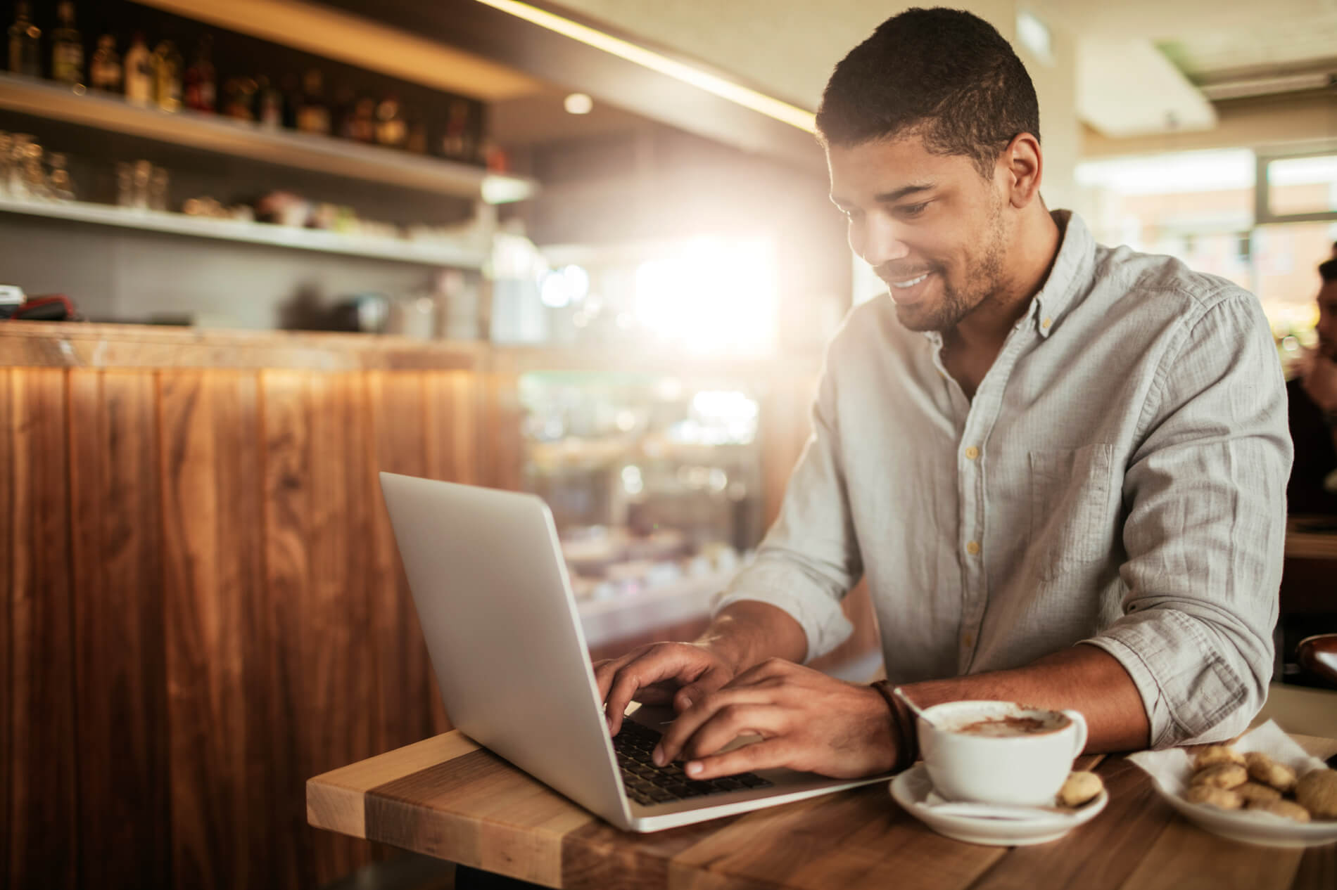 Man working on laptop with coffee and pastries in coffee shop