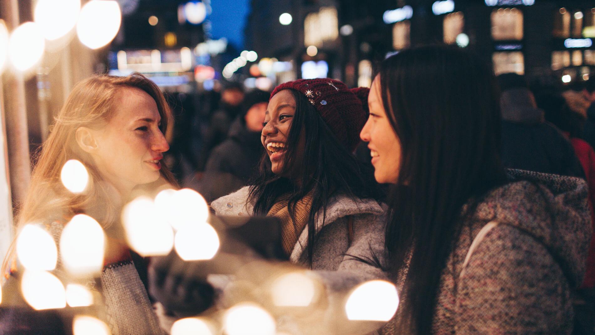 Three people talking at a sidewalk café