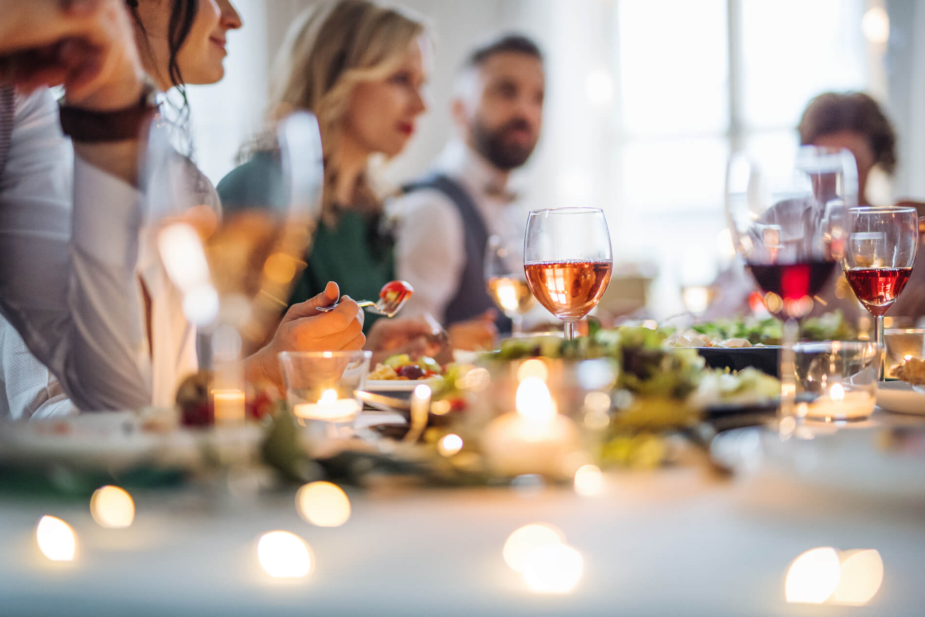 Several friends around festive table with food and wine