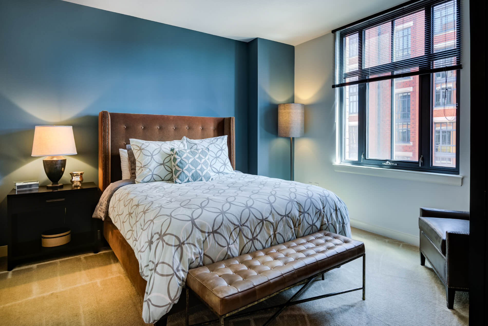 Bedroom with ample light, a big cushy bead and leather furnishings